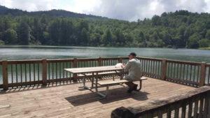 גבר יושב לפני שולחן בשפת אגם